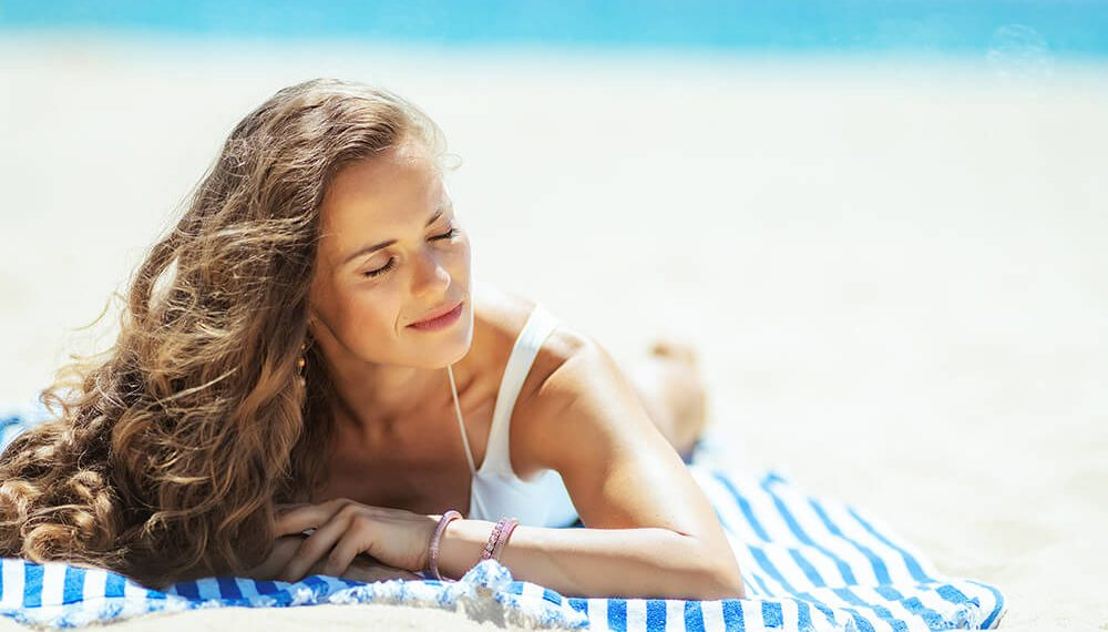 Žena se sunča na plaži
